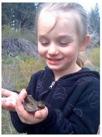 girl in a field holding a frog